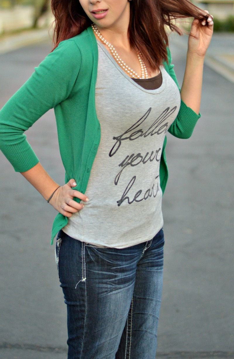 3 Ways to Style a Graphic Tee: This Follow Your Heart graphic tee pairs perfectly with a fitted and brightly colored cardigan. Add pearls and boot cut jeans with heels to dress up a tee to be a more professional and workplace friendly outfit // www.heytherechelsie.com
