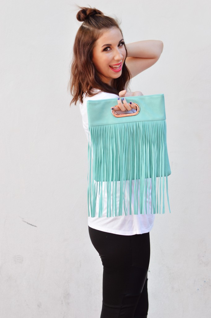 How to style edgy leggings: add a pop of color! Wearing black leggings and a loose tee is the perfect excuse to add a fun pop of color in an accessory, like this fringe aqua bag! // Hey There, Chelsie